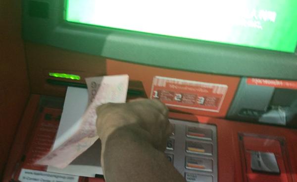 カシコン銀行ATMの利用明細書を受け取っているところ